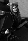 Black and white photo of a beautiful biker girl with a motorcycle royalty free stock images