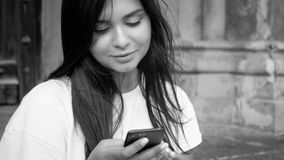 Black and white photo of beautiful brunette woman with long hair browsing internet on mobile phone royalty free stock images