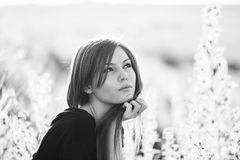 Black and white photo of beautiful girl with long, straight hair posing in the field Stock Image