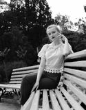 Black and white photo of a beautiful girl sitting on a bench. stock photography