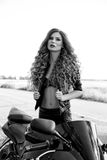 Black and white photo of a beautiful biker girl with a motorcycle stock photography