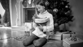 Black and white photo of beautiful smiling girl in sweater sitting with cat next to decorated Christmas tree royalty free stock images