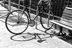A black and white pattern of a bike and its shade. A black and white photo of a bike and a bench on the background of the iron fence Stock Photos