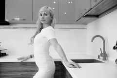 Black and white photo of blonde girl posing on camera in kitchen Stock Images