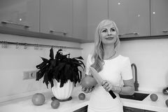 Black and white photo of blonde girl posing on camera in kitchen Royalty Free Stock Images