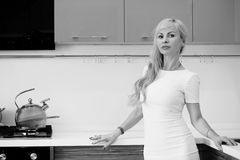 Black and white photo of blonde girl posing on camera in kitchen Royalty Free Stock Photography