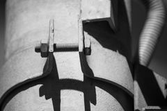 Black and white photo bolted metal pipe clamp. Monochrome photo bolted metal pipe clamp royalty free stock images