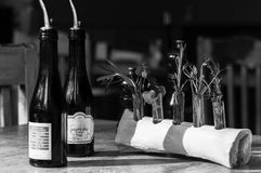 Black and white photo of bottles with olive oil in restaurant interior. Black and white photo. Glass bottle of olive oil on wooden table in steakhouse interior Stock Photos