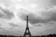 Black-and-white photo of the bottom of the Eiffel Tower and Pari. S in the background in cloudy summer day Stock Image
