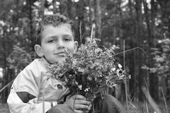 Black and white photo. The boy in the forest holding a bouquet o Stock Photography