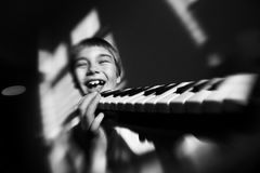 All this jazz. A black and white photo of a boy playing a melodic harmonica Royalty Free Stock Photos