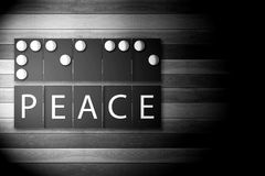 Black and White Photo of Braille Alphabet meaning of PEACE. Black and White Photo of Braille Alphabet meaning of PEACE in Bright Light on wooden Background Royalty Free Stock Photography
