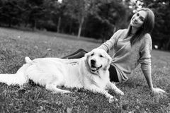 Black and white photo of brunette hugging labrador. On lawn in summer park Royalty Free Stock Photography