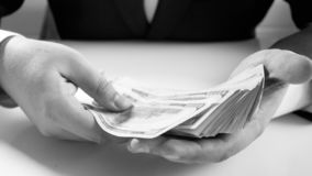 Black and white image of businessman holding big stack of money in hands. Black and white photo of businessman holding big stack of money in hands royalty free stock photos