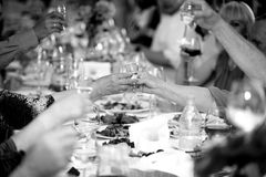 Black and white photo of celebrating people clinking glasses stock images