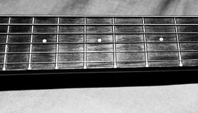 Black and white photo of a child`s acoustic guitar strings and frets on the neck of the guitar for music lessons royalty free stock photo