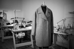 Black and white photo with a coat on a mannequin in a sewing wor Stock Images