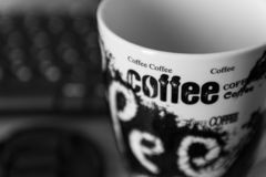 Black and white photo of a coffee mug in focus saying the words coffee. sharp. out of focus background stock photos