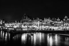 Black-white photo of cruise boat moving on night canals of Amsterdam in Amsterdam, Netherlands. Royalty Free Stock Image
