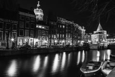 Black-white photo of cruise boat moving on night canals of Amsterdam in Amsterdam, Netherlands. Stock Image