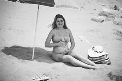 Black and white photo of cute pregnant woman sitting under paras Royalty Free Stock Images