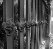 Black & white photo of decorative property fence. Detail view of floral medallions featured in residential fence Royalty Free Stock Photo