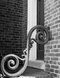Black & white photo of decorative scrollwork on porch. Detail view of decorative vintage scrollwork on porch of residential home near brick walls Stock Images