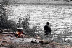 Black-and-white photo depicting fisherman, fire with tripod and cooking pot for cooking in autumn Royalty Free Stock Images