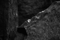 A Closeup Image of a Diamond Showing the Facets of the Gem on a Rock. A Black and White Photo of a Diamond with Blurred Scattered Diamonds, with a Blurred Rock stock photos