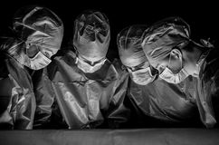 Black white photo of doctors in the operating room. Doctors are dressed in surgical suits, their faces have medical masks, and on their heads are surgical caps Stock Photo