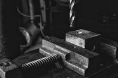 Black and white photo of drill bit coming down onto a piece of wood held in a vice in a workshop. Black and white photo of drill bit coming down onto a piece of stock photo