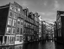 Black-white photo of famous buildings of Amsterdam city centre close-up at sun set time. Stock Photography