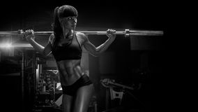 Black and white photo of fit young woman in great shape lifting Stock Photo