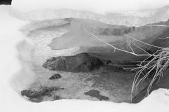 Black and white photo of frozen river and cracked snow cover on its banks Stock Image