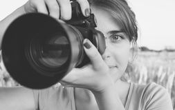 Black and white photo of the girl looking in the camera viewfinder in camera aimed at nature Royalty Free Stock Photo