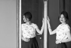 Black and white photo. The girl is seen from the side in the mirror. stock photo