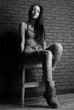 Black-and-white photo of a girl in top and jeans sitting on a stool against a brick wall, view from below. Vertical photo Stock Photos
