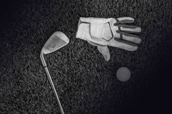 Black and white photo of golf clubs and a golf ball in low light. Black and white photo of golf clubs Royalty Free Stock Photos