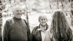 Elderly couple and young caregiver. Black and white photo of happy elderly couple and young caregiver Stock Images