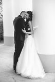 Black and white photo of happy just married couple kissing Stock Photos