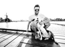 Black and white photo of a happy young man and his dog traveling together royalty free stock image