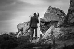 Black and white photo of kissing bride and groom on top of mount Stock Images