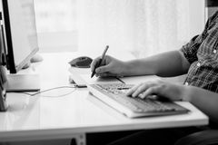 Black and white image of male designer using graphic tablet at office. Black and white photo of male designer using graphic tablet at office Royalty Free Stock Image