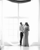 Black and white photo of man hugging pregnant wife against windo Royalty Free Stock Photos