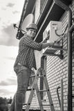 Black and white photo of man repairing air conditioner standing. Black and white photo of young man repairing air conditioner standing on ladder Royalty Free Stock Images