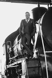 Black and white photo of man in retro suit standing on old locomotive stock photography