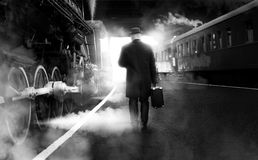 Black and white photo of man in vintage clothes walking on railway station stock images
