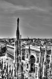 Black and white photo of marble statues of Cathedral Duomo di Milano on piazza, Milan cityscape and Galleria Vittorio Emanuele II Royalty Free Stock Photography