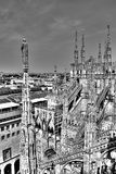 Black and white photo of the marble statues, spires and stone sculptures on the roof of famous Cathedral Duomo and cityscape Stock Photos