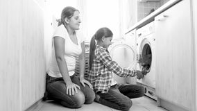 Black and white photo of mother with daughter doing housework at laundry royalty free stock photography